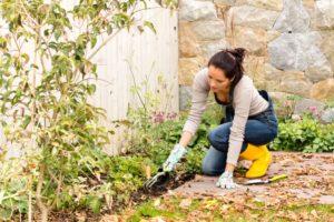 Young woman autumn gardening backyard planting tools housework flowerbed